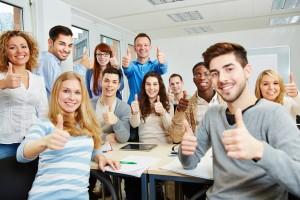 Viele glückliche Studenten halten Daumen hoch mit dem Dozent in der Uni
